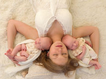 Tender mother and identical twins Stock Images