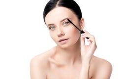 Tender naked brunette woman applying mascara. Isolated on white Stock Image