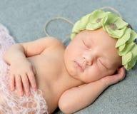 Tender newborn sleeping with wreath on head Stock Photo