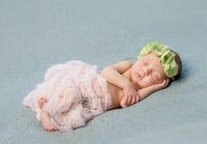 Tender newborn sleeping with wreath on head Stock Image