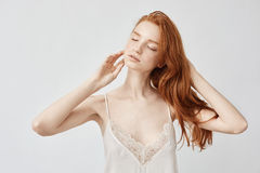Tender nude redhead model posing with closed eyes. Tender nude redhead model in sleep underwear posing with closed eyes. Copy space. White background Stock Image