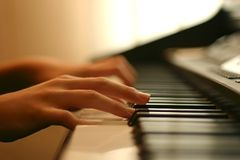 Tender piano music. Close-up of a piano player hands gently touching the keys Royalty Free Stock Photo