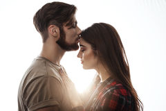 Tender picture of young couple. Man kissing woman to forehead. Royalty Free Stock Images