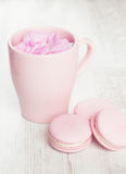 Tender pink macaroons and tea cup on white wood background Stock Images