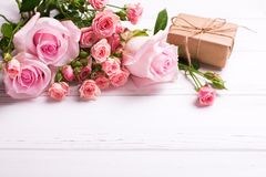 Tender pink roses flowers  and  wrapped box with present on whit Royalty Free Stock Image
