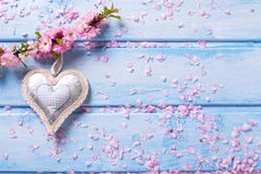 Tender pink  sakura flowers and decorative heart on blue wooden Stock Image