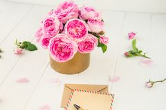 Tender pink tea roses bouquet in vintage pot, blank of greeting card and craft paper envelope on white wooden background. Postcard. Mock up. Summer, spring royalty free stock image