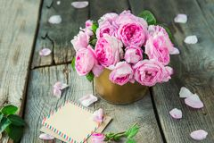 Tender pink tea roses bouquet in vintage pot and blank of greeting card on rustic old wooden table. Floral background. Postcard mo. Ck up. Summer, spring flowers royalty free stock photography