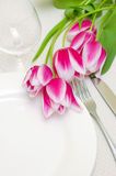 Tender pink tulips grace a table setting Royalty Free Stock Photography
