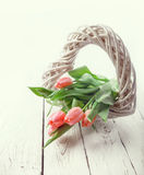 Tender pink tulips with rustic wooden heart Stock Images