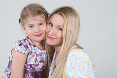 A tender portrait of a mother and daughter. Huddled together in the studio royalty free stock images