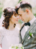 The tender portrait of the newlywed couple is standing head-to-head. Royalty Free Stock Images