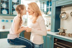 Pleased young woman holding hands of her kid stock photos