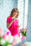Tender pregnant girl in bright pink dress at the window Stock Photos