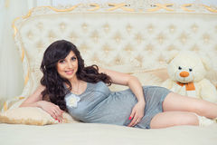 Tender pregnant in gray dress on the bed  hugging tummy Royalty Free Stock Photos