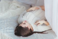 Tender pregnant woman lying on bed covered with tule canopy Royalty Free Stock Images