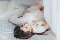 Tender pregnant woman lying on bed covered with tule canopy Royalty Free Stock Photography
