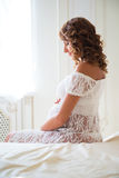 Tender pregnant woman sitting on bed and hugging tummy Royalty Free Stock Photos