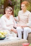 Tender professional caregiver in uniform putting her hand on a s. Houlder of an elderly women during snack time on a patio of a senior home. Blurred background stock photo