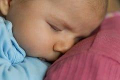 Tender scene: Cute peaceful baby boy sleeping in mothers arms. Stock Image