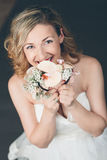 Tender shy young bride hiding in her flowers. Tender shy young bride hiding in her bouquet of flowers looking up at the camera with a radiant smile of happiness Royalty Free Stock Image