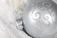 Tender silver Christmas bauble on to snow. Royalty Free Stock Image