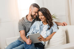 Tender smiling couple with digital tablet sitting on sofa Royalty Free Stock Images