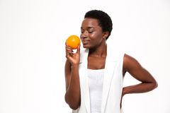 Tender smiling young woman with closed eyes smelling fresh orange Royalty Free Stock Photo