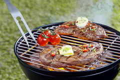 Tender steak grilling on a barbecue Royalty Free Stock Photos
