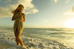 Tender Venus Morning. Morning suns rays is flattering a beautiful woman who is innocently wading inshore of the ocean Royalty Free Stock Images