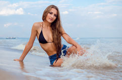 Tender wave. Girl with long hair sitting on the beach, and wave splashing on her legs royalty free stock image