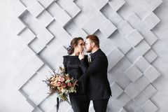 Tender wedding couple posing on gray geometric background in studio.  Stock Photos