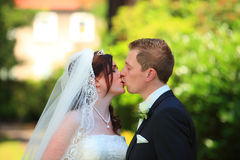 Tender wedding kiss. Young couple is kissing each other after wedding. wedding kiss Royalty Free Stock Image
