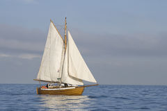 Tender with white sails. In the calm sea stock photo