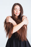 Tender woman with beautiful long hair standing and hugging herself Stock Photos