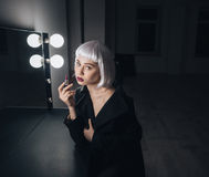 Tender woman in blonde wig applying lipstick near the mirror Royalty Free Stock Image
