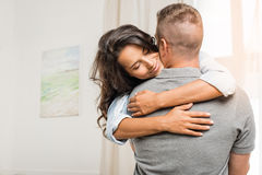 Tender woman with closed eyes embracing her boyfriend at home Royalty Free Stock Image