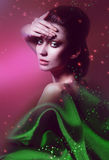 Tender woman in green fabric. On pink background Royalty Free Stock Images