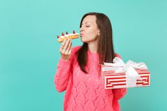 Tender woman in pink sweater with closed eyes holding eclair cake, red present box with gift ribbon isolated on blue. Background. Valentine`s, Women`s Day stock images