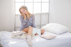 Tender woman relaxing and listening to music from tablet. Tender pretty blond woman in pajamas and knitted socks relaxing in bed and listening to music from Stock Image