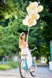 Tender woman on vintage bicycle with balloons looks with smile. A tender woman on a vintage bicycle with balloons in her hands looks around with a smile back to Royalty Free Stock Photos