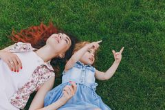 Tender woman in light dress and little cute child baby girl pointing index fingers up lie on green grass in park. Mother. Tender women in light dress and little stock images