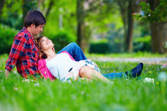 Tender young couple relaxing on spring meadow Stock Photos