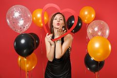 Tender young girl in black dress holding big red wooden heart, blowing lips, sending air kiss on red background air stock photos