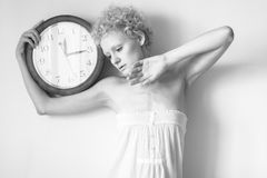 Tender young girl with curly hair and a big clock in his hands. Stock Photos
