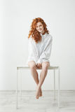 Tender young redhead girl in shirt sitting on table over white background smiling looking at camera. Stock Photography
