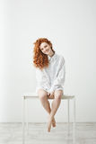 Tender young redhead girl in shirt sitting on table over white background smiling looking at camera. Royalty Free Stock Photography