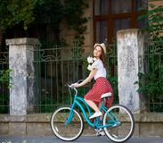 Tender young woman on blue retro bike with peonies. Tender young woman on a blue retro bike with peonies. A girl in a red skirt with polka dots and a hat on her Royalty Free Stock Images
