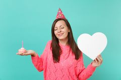Tender young woman in knitted pink sweater, birthday hat with closed eyes hold cake with candle, white heart with copy. Space isolated on blue background stock photography
