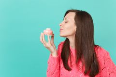 Tender young woman in knitted pink sweater keeping eyes closed, hold in hand and sniff cake isolated on blue turquoise. Wall background, studio portrait. People royalty free stock images